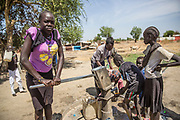 Students fetch water from a well at the Machakos Primary School in Bentiu, South Sudan. After two years of closure due to threats from unexploded ordnance, UNMAS surveyed and cleared the school compound in July 2015 allowing the school to reopen and the pupils to return to their studies.<br />