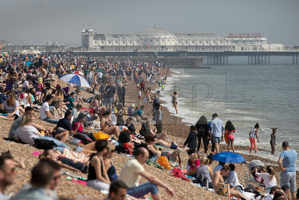 © Licensed to London News Pictures. 22/04/2019. Brighton and Hove, UK. Sun seekers crowd the beach at Brighton, West Sussex. Most of the UK is enjoying record breaking high Easter weekend temperatures. Photo credit: Peter Macdiarmid/LNP
