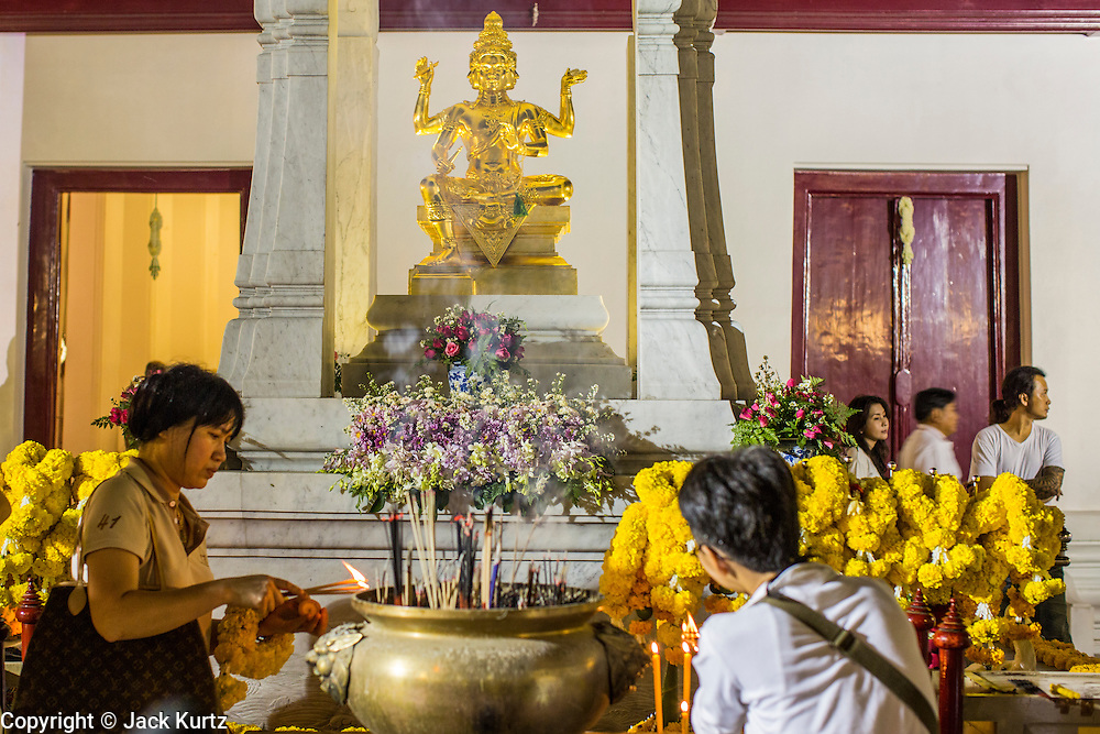 27 JANUARY 2013 - BANGKOK, THAILAND:  People pray at the entrance to the temple for Thaipusam at Dhevasathan (the Brahmin Shrines) on Dinso Rd in Bangkok. Thaipusam is a Hindu festival celebrated primarily by the Tamil community in South East Asia on the full moon in the Tamil month of Thai (Jan/Feb). Pusam refers to a star that is at its highest point during the festival. The festival commemorates both the birthday of the Hindu god Murugan, son of Shiva and Parvati, and the occasion when Parvati gave Murugan a vel (a lance) so he could vanquish the evil demon Soorapadman. The holy day is celebrated by Brahmins in Thailand. Brahmanism was the court religion before Buddhism came to Thailand and before the foundation of Sukhothai. Both religions are combined in the Thai way of life and its customs and ceremonies.       PHOTO BY JACK KURTZ
