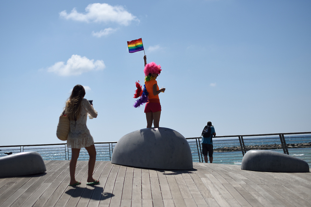 TEL -AVIV, ISRAEL - June 12, 2015: A Participant of the Annual Gay Pride Parade poses for a picture as she holds a rainbow flag in Tel-Aviv, June 12, 2015. The parade, celebrated as part of Tel-Aviv Pride Week events, attracted many thousands of participants from all over the world. Photo by Gili Yaari