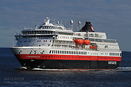 Hurtigruten cruise ship, Finnmarken, sails along coast toward Havoysund  in early May; Norway.