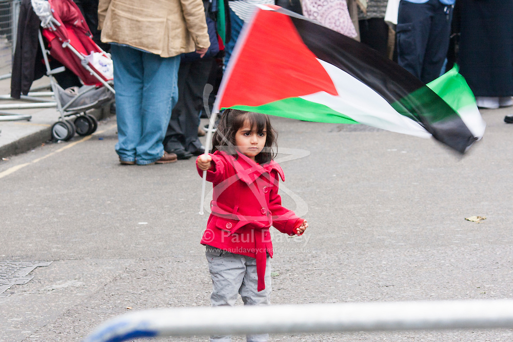 Kesnington, London, July 11th 2014. A little girl plays with a Palestinian flag as thousands of Palestinians and their supporters demonstrate against the latest wave of Israeli retaliatory attacks on Palestinian targets and homes, where casualties are steadily mounting.
