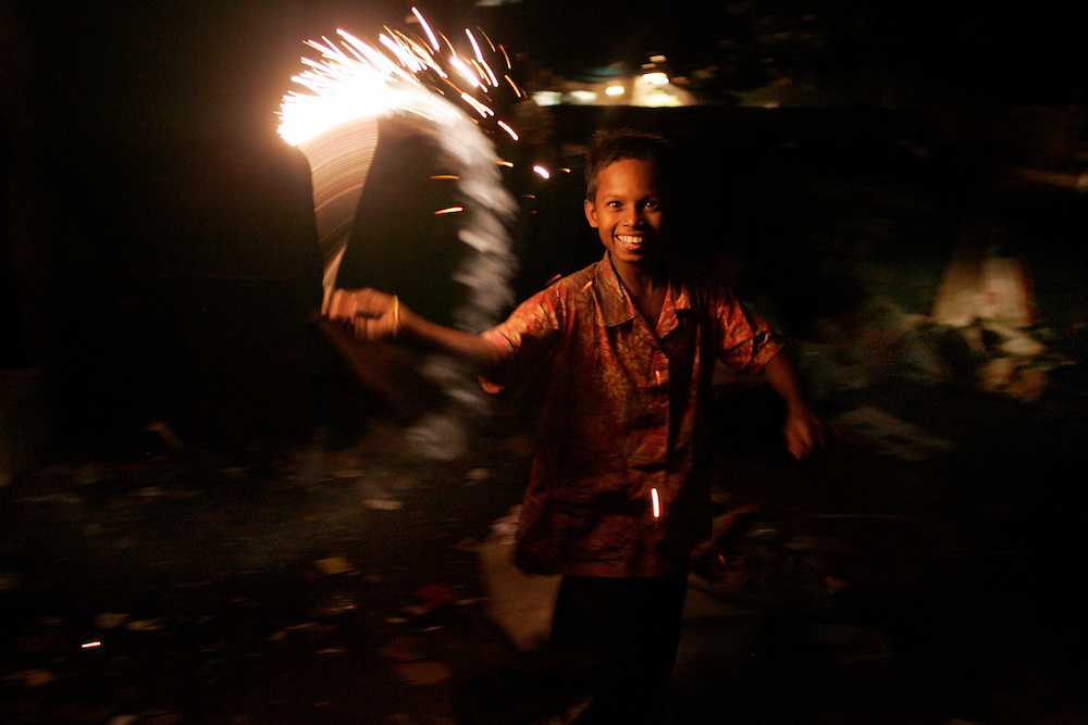 A young boy holds a firework during Diwali Day in New Delhi, India.