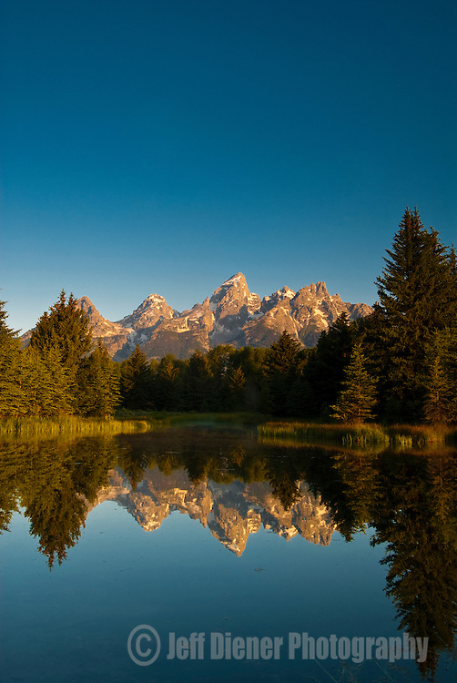 The Tetons are reflected at sunrise in Grand Teton National Park, Jackson Hole, Wyoming.