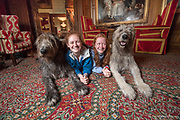 Two redheaded girls lay on the ground with two Irish Wolfhounds inside Ashford Castle, a 13th century castle turned into a 5 star luxury hotel located in Cong, Ireland.