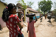 Pooja, 14, a student from the village of Pathpuri, Hoshangabad, Madhya Pradesh, India, taking part to the children's journal, a project launched by Dalit Sangh, an NGO which has been working for the uplift of scheduled castes for the past 22 years, is photographing a young villager on her daily chores with a digital camera provided by the project to child reporters. Dalit Sangh is working in collaboration with Unicef India to promote education and awareness within backward communities.