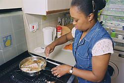 Woman standing at cooker in kitchen cooking fish in frying pan,