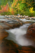 The Swift River flows into Rocky Gorge, lined by a variety of trees displaying their fall colors in the White Mountains, New Hampshire..
