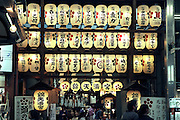 People pass in front of a street temple entrance in Kyoto