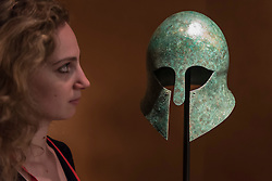 © Licensed to London News Pictures. 29/06/2016. London, UK.  A woman views a bronze, sixth century BC, Greek Corinthian helmet at the preview, in Chelsea, of Masterpiece London, the leading international fair for art and design from antiquity to the present day with works from 154 world-renowned exhibitors on sale.  The fair is open until 6 July.Photo credit : Stephen Chung/LNP