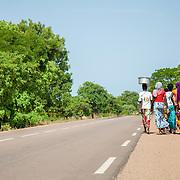 LÉGENDE: La route réhabilité par la BAD qui rélie N'Djaména - Koumra  et Sarh. Un groupe de jeunes femmes marche près du bord de la route. LIEU: Koumra, Tchad. PERSONNE(S): N/A.