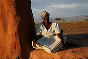 A woman smiles at the camera by her home in Damaraland. Namibia..© Zute and Demelza Lightfoot.www.lightfootphoto.com