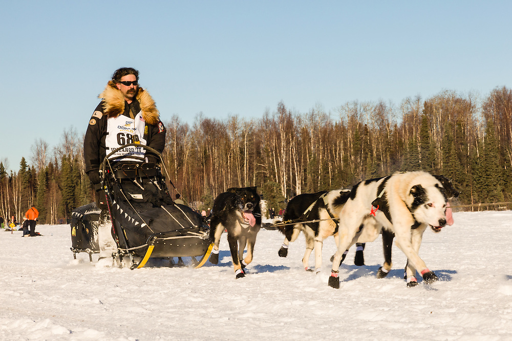 Musher Mike Santos competing in the 42nd Iditarod Trail Sled Dog Race on Long Lake after leaving the restart on Willow Lake in Southcentral Alaska.  Afternoon. Winter.