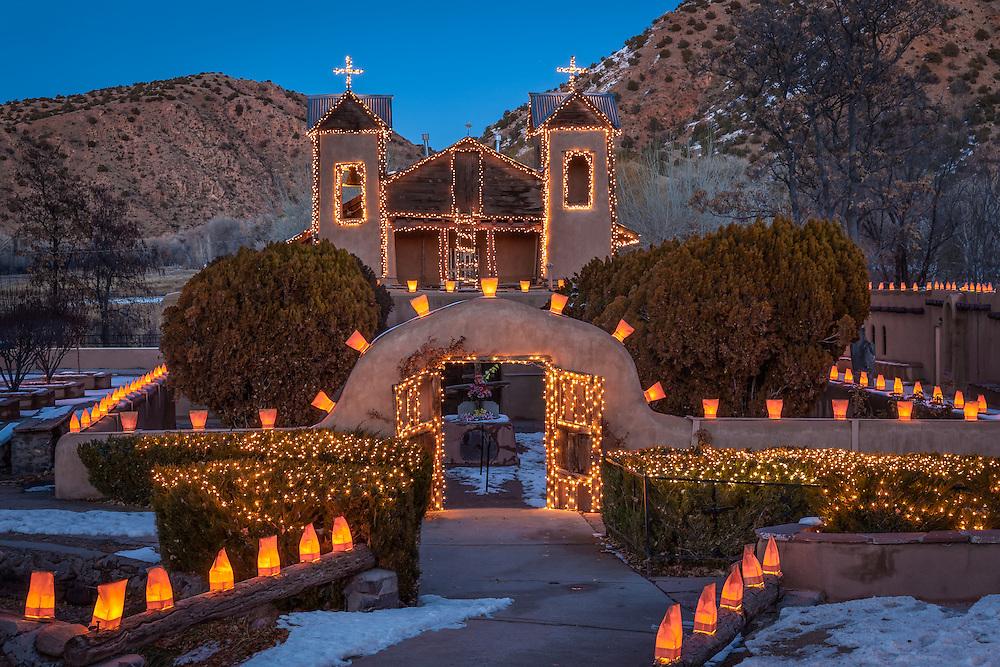 Christmas lights and luminarias adorn El Santuario de Chimayo, a National Historic Landmark nestled in the Sangre de Cristo Mountains north of Santa Fe, New Mexico.