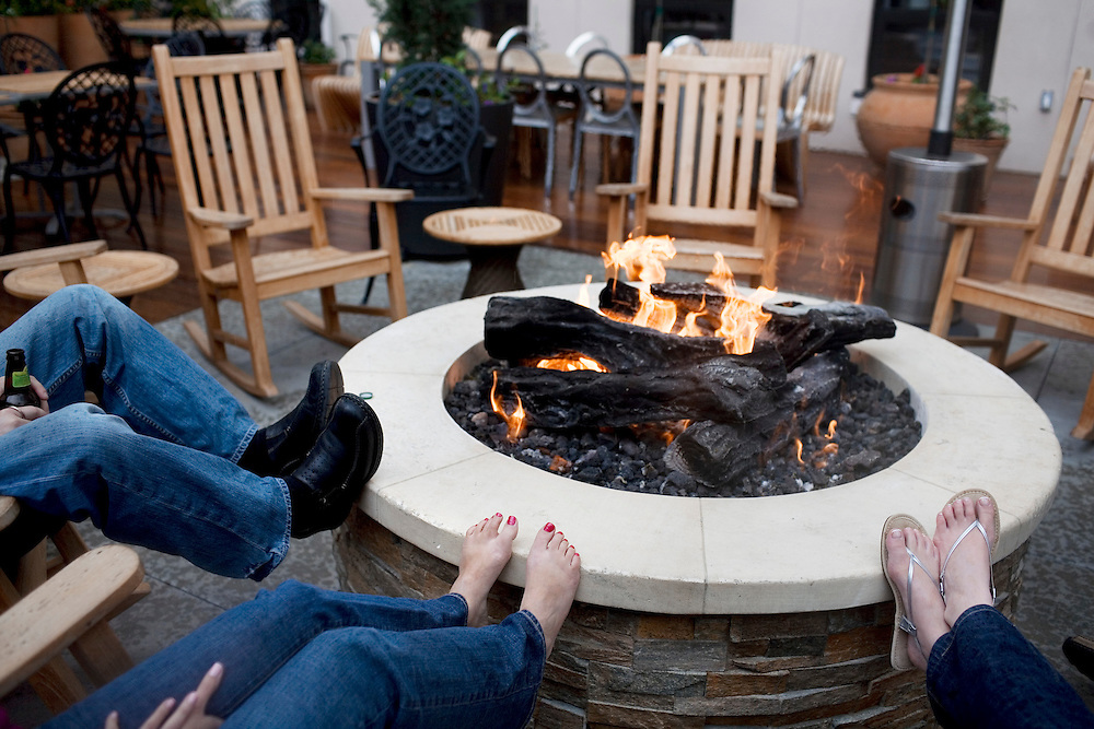 """Brett and Sarina Fleischer, left, and Andrea Theriault, of Connecticut, warm up by the fire pit on the second floor rooftop of Avia Napa, a new boutique hotel that opened last year, in Napa, Ca., on Saturday, May 22, 2010. Recent development along First Street includes a new boutique hotel, restaurants, and tasting rooms has helped revitalize Napa's downtown, which has recently been coined the """"West End."""""""