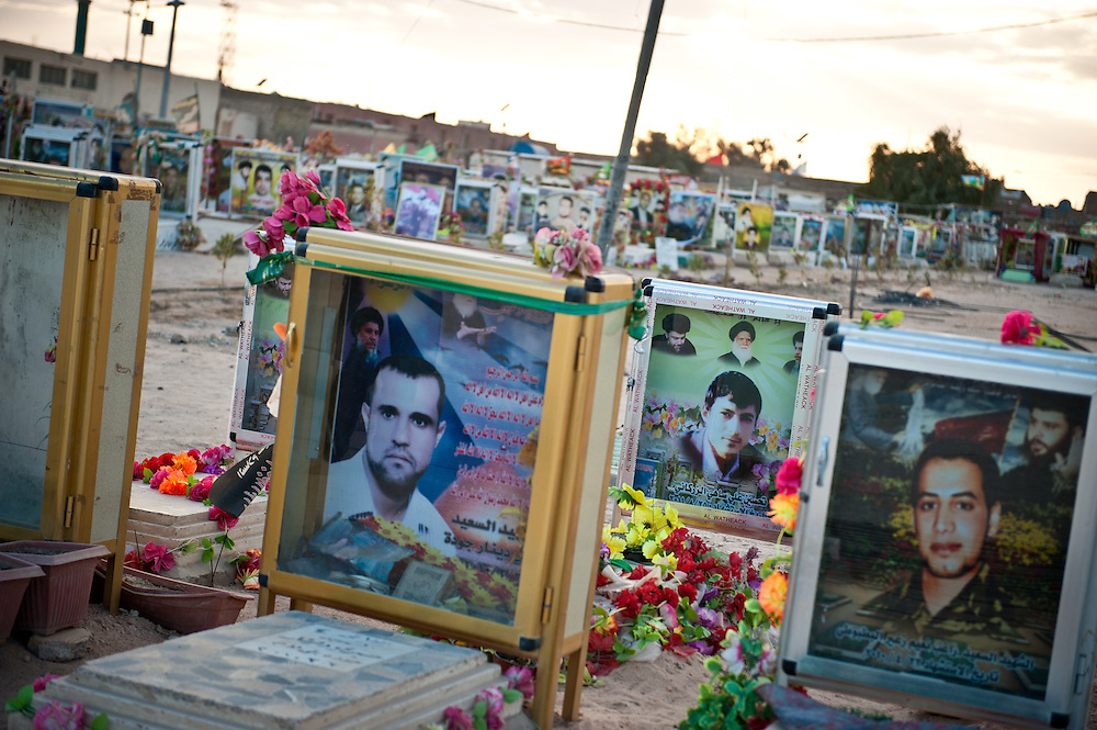 """Photographs of dead Mahdi Army """"martyrs,"""" who died fighting the American army or the Sunni militias, adorn their graves in a special section of the Najaf Cemetery."""