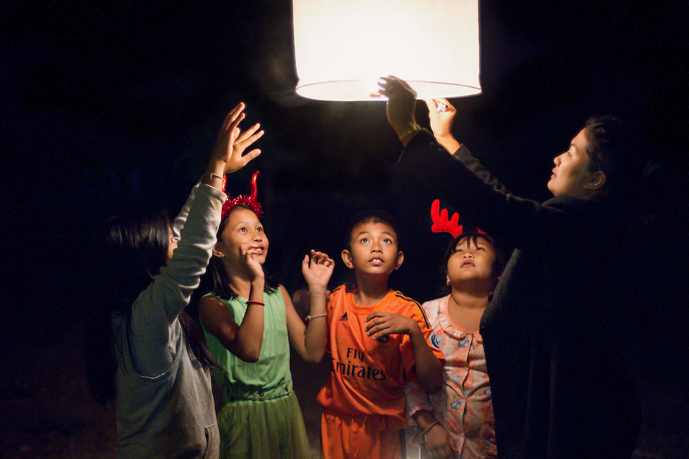 A Thai family releases a sky lantern to celebrate 2015 in rural Thailand.