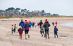 Pictured: Santa Beach Run on the scenic East Lothian coast. This new event is aimed at athletes, casual runners and families. It is hosted by Project Trust with proceeds enabling local school leavers to spend a year volunteering in India/Honduras to teach at a school with few teaching materials. The children's 2lm race sets off across the beach. 15 December 2018  <br /> <br /> Sally Anderson | EdinburghElitemedia.co.uk