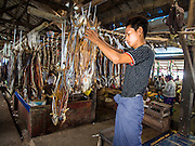 08 NOVEMBER 2014 - SITTWE, RAKHINE, MYANMAR:  A vendor hangs dried fish in his stall in the market in Sittwe. Sittwe is a small town in the Myanmar state of Rakhine, on the Bay of Bengal.  PHOTO BY JACK KURTZ