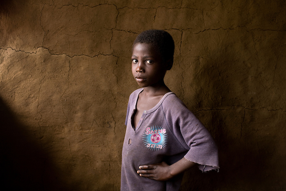 """Abenigo, """"I like this shirt because it has a football on it. I like to play football. I have three shirts and this one is the nicest. On the back there is a number. My Mama bought it for me."""" Freemans reserve, Kingsville, Liberia, West Africa."""