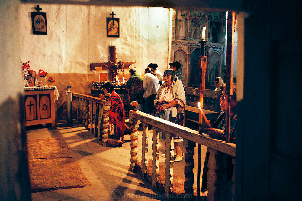Visitors from Zia Pueblo, San Isidro inside of the Chimayo Sanctuary on the road to Taos, near Santa Fe, New Mexico, USA. It is dedicated to the Madonna where supposedly a miracle occurred.