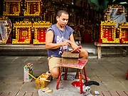 31 JULY 2018 - BANGKOK, THAILAND: An artisan on Phlap Phla Chai Road in Chinatown paints a Chinese character for a home. Bangkok's Chinatown district is one of the largest Chinatowns in the world. It was established in 1781 when Siamese King Rama I gave the Chinese community in Bangkok land outside of Bangkok's city walls so he could build his palace (what is now known as the Grand Palace). Chinatown is now the heart of the Thai-Chinese community. About 14% of Thais have Chinese ancestry.    PHOTO BY JACK KURTZ