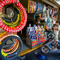 Jan 3, 2013 - A repair shop owner displays new tires for all sorts of two wheel cycles in the Cambodian capital city of Phnom Penh.<br /> <br /> Story Summary: Amidst the feverish pace of Phnom Penh&rsquo; city streets, a workhorse of transportation for people and goods emerges: Bicycles, motorcycles, scooters, Mopeds, motodups and Tuk Tuks roam in place of cars and trucks. Almost 90 percent of the vehicles roaming the Cambodian capital of almost 2.3 million people choose these for getting about. Congestion and environment both benefit from the small size and small engines. Business is booming in the movement of goods and and another one million annual tourists in Cambodia&rsquo;s moto culture.