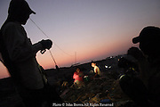 "Two male workers have a bit of fun shining their flashlights on the faces of two female workers at the Stung Meanchey Landfill in Phnom Penh, Cambodia. The landfill is nicknaned ""Smokey Mountain""."