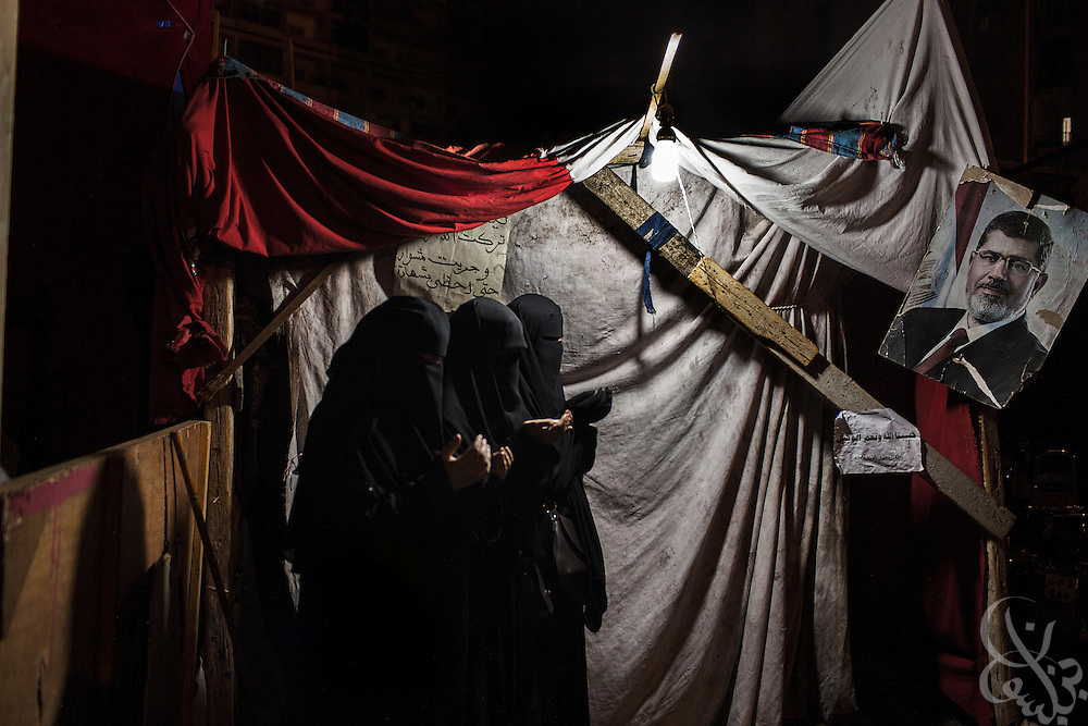 Egyptian women pray together outside their tent during Fajr (dawn) prayers at the Rabaah al-Adawiya protest camp Monday, August 12, 2013 in the Nasr City District of Cairo, Egypt. Morsi supporters and other groups opposed to the military coup in Egypt have been occupying the camp for more than a month and are now on high alert because they believe authorities might move in soon to forcibly break up the sit-in.
