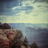 A couple looking across the Grand Canyon in USA with clouds in a blue summer sky with texture layer