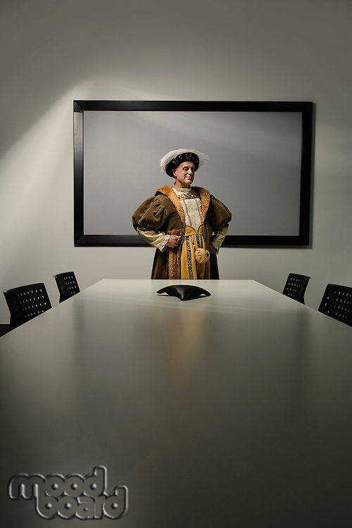 King Henry VIII standing at table in conference room