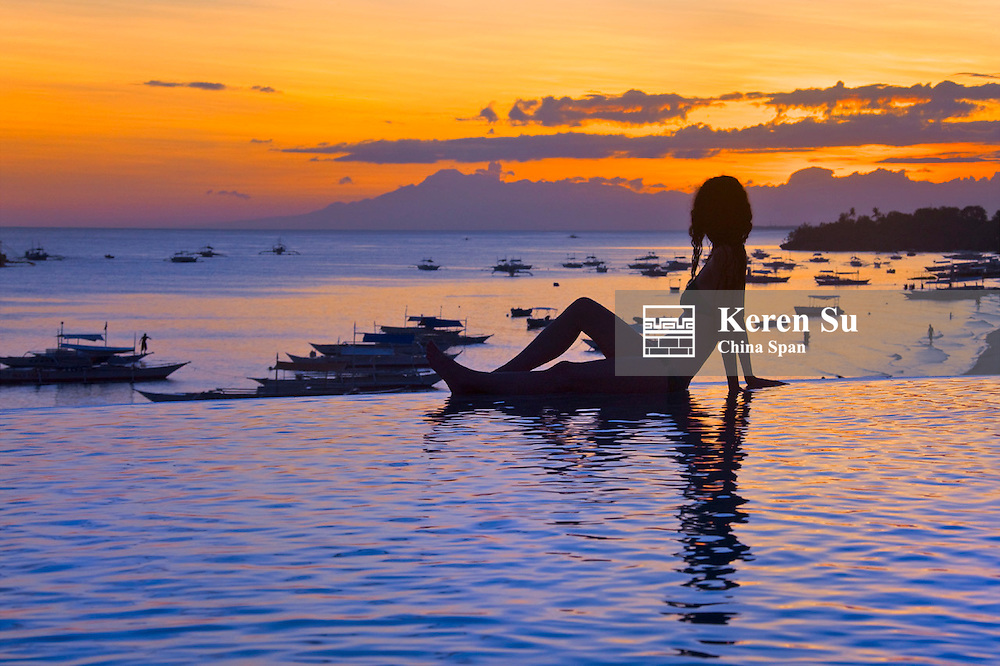 Woman in bikini on the beach at sunset, Bohol Island, Philippines