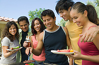 Group of young people gathered around grill at outdoor picnic.