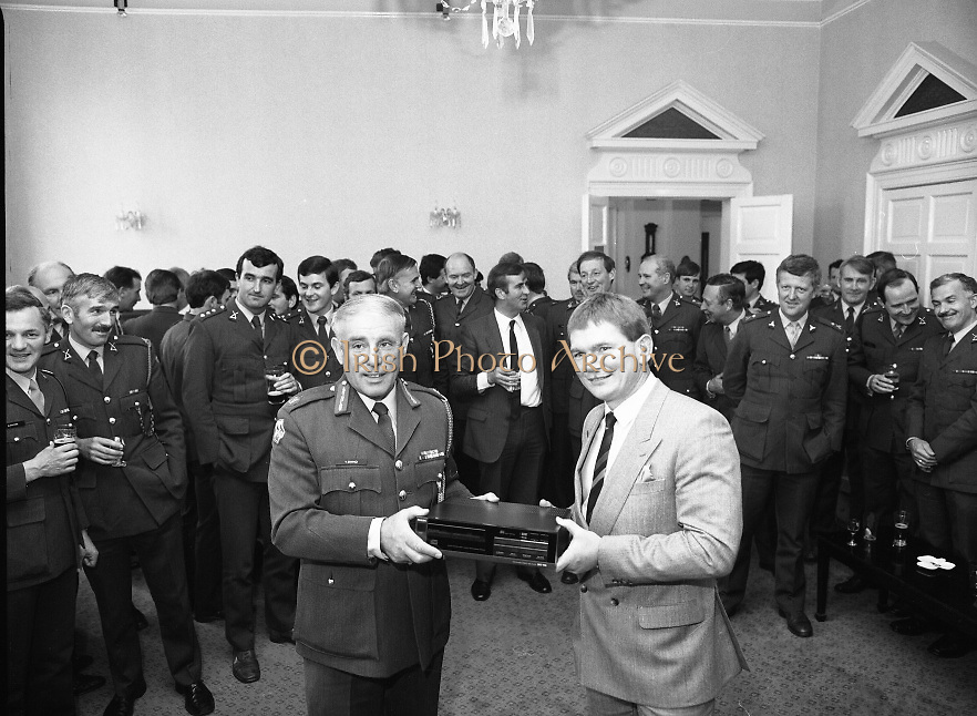 Ciaran Fitzgerald Honoured..1986..05.09.1986..09.05.1986..5th September 1986..To mark his retirement from the Defence Forces, Ciaran Fitzgerald was presented with a Hi-fi system by his colleagues. Ciaran is a noted rugby player and has captained Ireland in many international matches...Photograph of the presentation of a hi-fi unit being made to Ciaran Fitzgerald. The presentation was carried out by Brig General, Vincent Savino. In the background are some of Ciarans' friends and colleagues who attended the function.