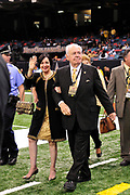 "World Champion New Orleans Saints owner Tom Benson struts on the field sporting a one of a kind hand made ""special ""pinstripe suit"" The striping says "" New Orleans Saints World Champions"" all over the  Black & Gold Suit!!! His wife Gayle , on his arm,had it made for him as a surpirse and he was presented it right before opening of the NFL season in New Orleans Louisiana Thurs Sept. 9,2010. The Saints beat the Minnessota Viking 14-9. Phot © Suzi Altman"