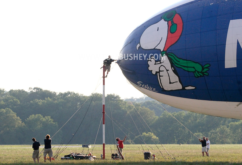 Montgomery, NY - Members of the ground crew control the MetLife blimp Snoopy Two as it approaches the mooring mast at Orange County Airport on July 25, 2008.