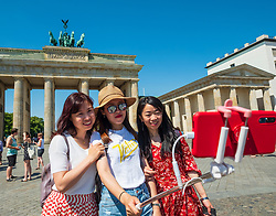 Female Chinese tourists posing with selfie stick in frontt of Brandenburg Gate in Berlin, Germany