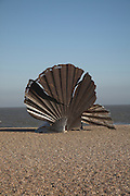 """The Scallop, sculpture by Maggi Hambling is dedicated to Benjamin Britten, who used to walk along the beach in the afternoons. Created from stainless steel by Suffolk-based artist Maggi Hambling, it stands four metres high, and was unveiled in November 2003. The piece is made up of two interlocking scallop shells, each broken, the upright shell being pierced with the words: """"I hear those voices that will not be drowned"""", which are taken from Britten's opera Peter Grimes. The sculpture is meant to be enjoyed both visually and tactilely, and people are encouraged to sit on it and watch the sea."""