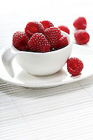 Raspberries in white cup - studio shot