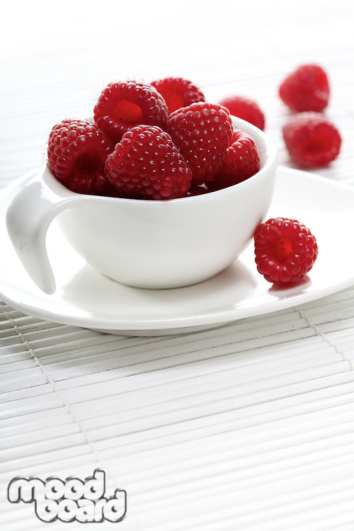 Raspberries in white cup - studio shot