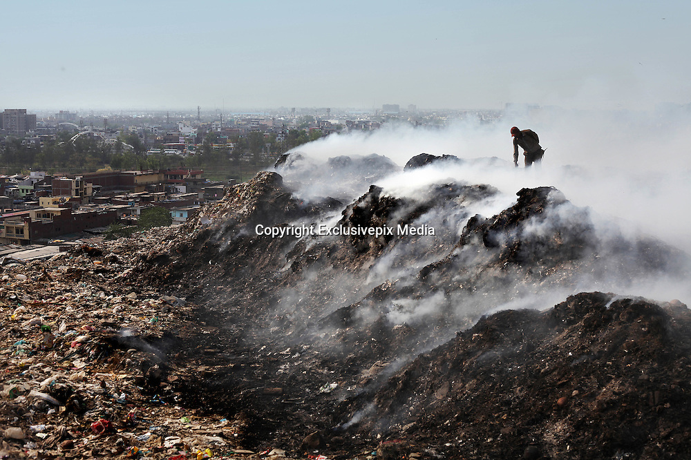 New Delhi, India - <br /> <br /> Garbage Mountain<br /> <br /> Just a few miles from the famous Akshardham temple, where tourists flock to see the structure's sandstone and marble work, the 29-hectare, slum-surrounded Ghazipur landfill in east Delhi seems a world apart. Each day hundreds of mainly migrant workers earn a meager living at the landfill by collecting recyclable material like plastic, metal and even hair to sell. The dump is the last port of call for Delhi's trash, having already been picked through by other waste collectors who collect bags of garbage directly from homes. Delhi is home to three landfills where around 6,000 tons of trash is dumped daily. Studies have shown that living near a landfill increases the risk of cancer, birth defects and asthma.<br /> <br /> Photo shows: Amidst a thick blanket of smoke, a rag picker sifts through a pile of rubbish to pick out pieces of glass, metal and plastic at the Ghazipur landfill. <br /> &copy;Chinky Shukla/Exclusivepix Media