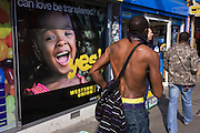 A shirtless black man walks past a Western Union street ad poster.