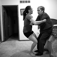 Mt. Laurel, NJ - Elizabeth Wolf, 35, lifts her mother, Nancy Brood, 65, to her feet after giving her a shower.  Wolf moved home to New Jersey 5 years ago and has been caring full-time for her parents who both have Alzheimer's.
