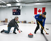 Tim Egan plays a shot and Jeff Pulli assists during a match at Rochester Curling Club on Sunday, February 8, 2015.