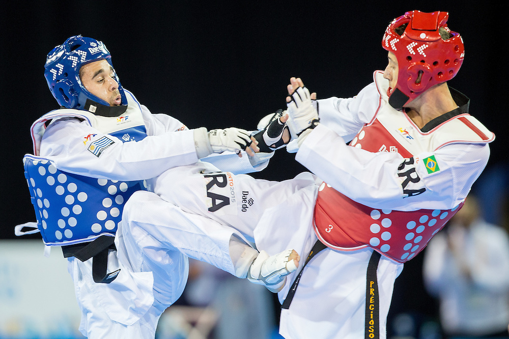 Federico Gonzales of Uruguay and Henrique Precioco of Brazil trade kicks during their 1/8 round contest in the -68kg weight class of Taekwondo at the 2015 Pan American Games in Toronto, Canada, July 20,  2015.  AFP PHOTO/GEOFF ROBINS