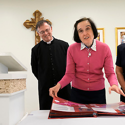 30 APRIL 2016 -- WENTZVILLE, Mo. -- Gianna Emanuela Molla (second from right), daughter of St. Gianna Beretta Molla, reviews a photo album of &quot;Gianna Baby Families&quot; with Mary Williams (left), Father Timothy Elliott and Connie Quinn during a reception following Mass at St. Gianna Catholic Church in Wentzville, Mo. Saturday, April 30, 2016. The event honored the visit of Molla and marked the 10th anniversary of the founding of St. Gianna Parish.<br /> <br /> Photo by Sid Hastings.