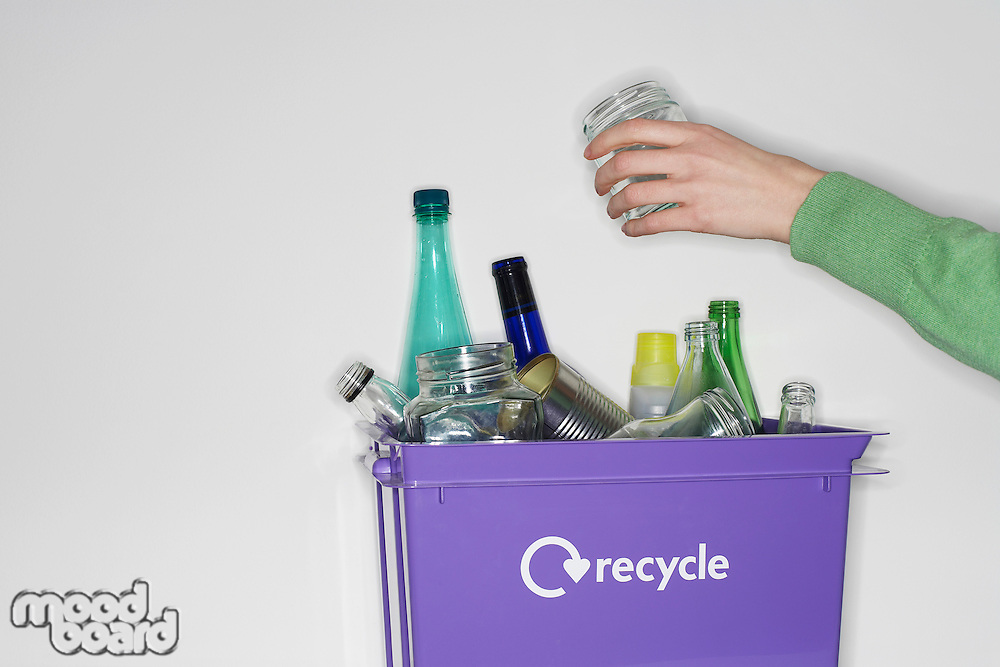 Person putting jar into recycling container filled with empty glass vessels
