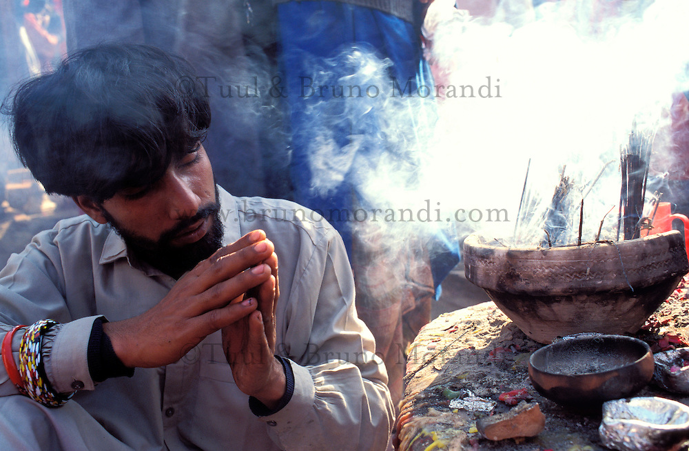 Pakistan - La fête des soufis - Province du Sind - Sehwan e Sharif - Tombe du saint soufi Lal Shabaz Qalandar - Fête de l'anniversaire de sa mort (Urs) - Ce pelerins venere la tombe d'un des disciple (derviche) du saint, mains jointes et encens // Pakistan, Sind province, Sehwan e Sharif, Sufi saint Lal Shabaz Qalandar shrine, annual Urs festival