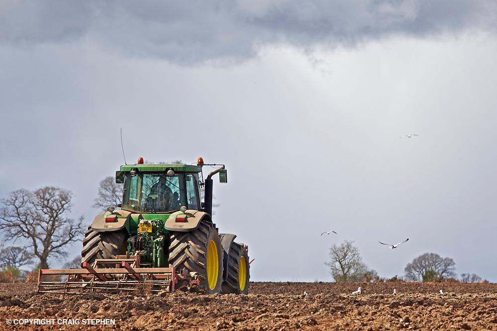 John Deere tractor harrowing a ploughed field against skyline