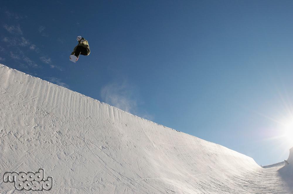 Silhouette of teenage snowboarder on halfpipe